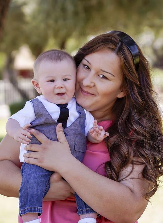 Assistante maternelle qui porte bébé dans bras tout sourire