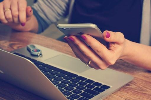 Femme devant ordinateur avec téléphone portable