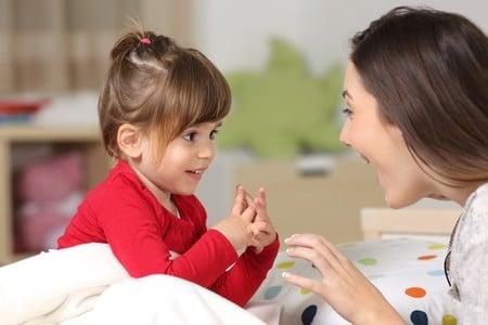 Nounou qui fait des jeux de doigts avec petite fille