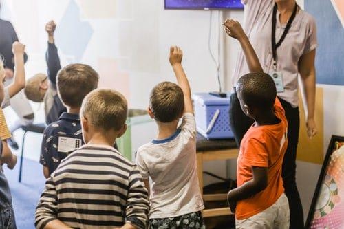 Enfants qui lèvent le doigt pour parler en classe