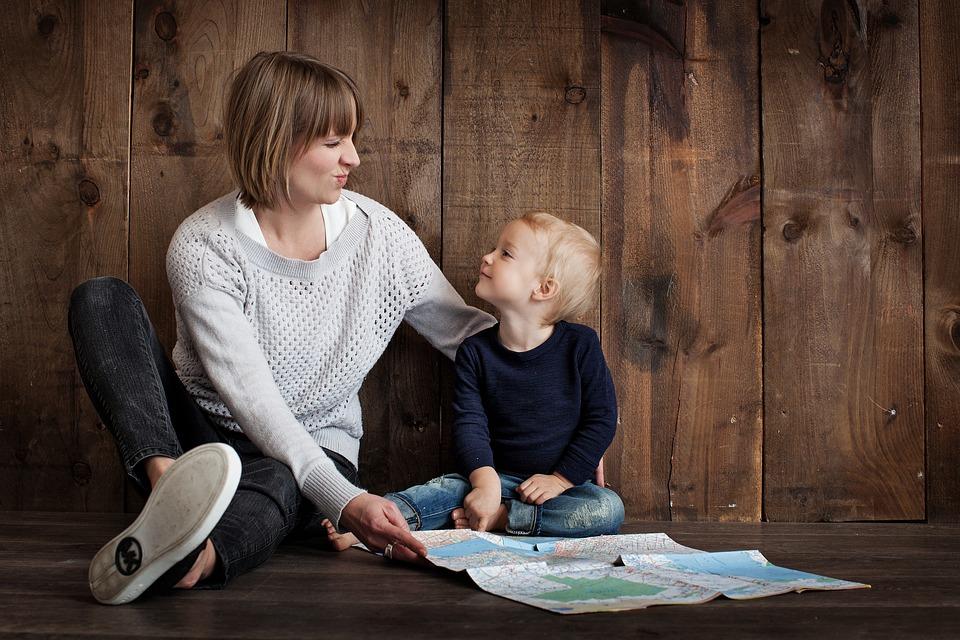 Maman qui joue avec son enfant au sol avec une carte du monde