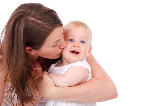 Femme qui embrasse bébé sur la joue