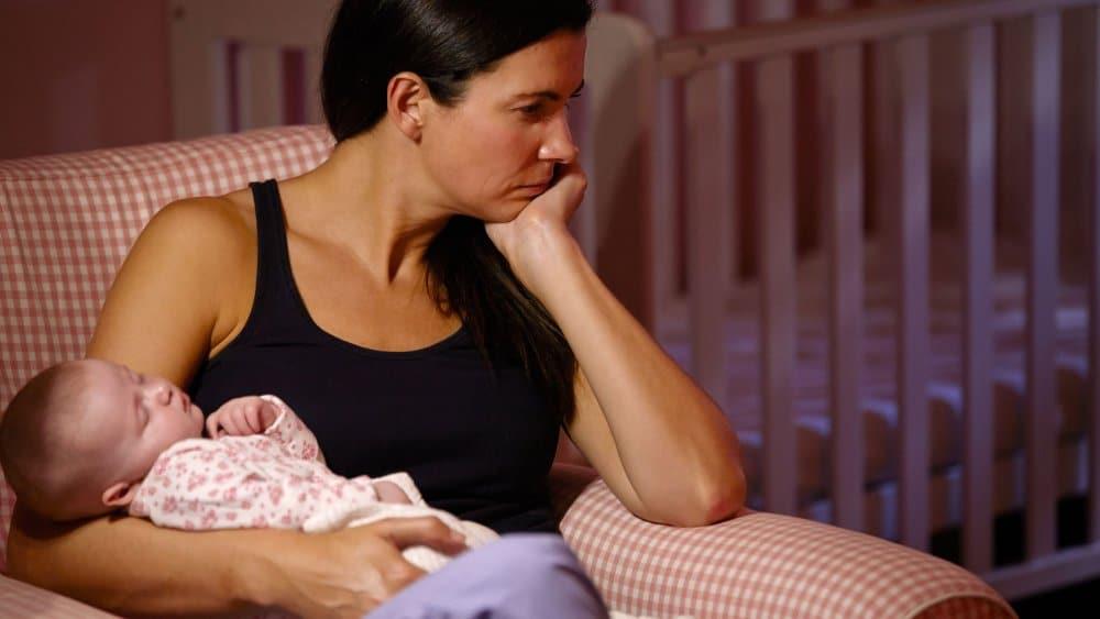 Maman triste qui tient bébé qui dort dans ses bras