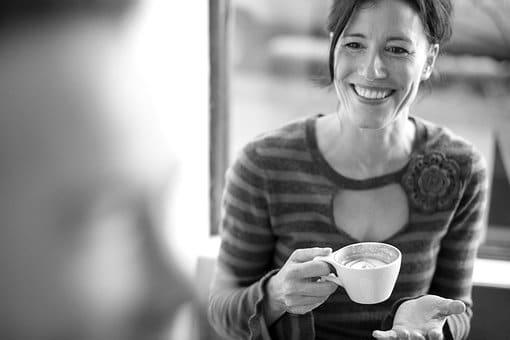 Femme qui sourit à quelqu'un en tenant une tasse de café