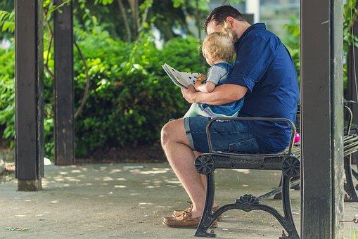 Nounou homme qui lit un livre à bébé au parc