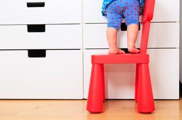 Jambes de bébé debout sur petite chaise rouge