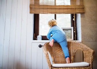 Enfant qui grimpe sur le dossier d'un fauteuil