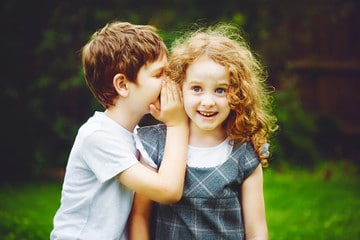 Petit garçon dit secret à petite fille