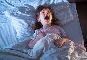 Petit fille qui hurle couchée dans son lit